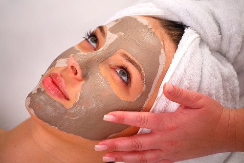 Spa clay mask on a woman's face, white background